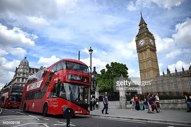 Red London buses travel past the Elizabeth Tower which houses the 'Big Ben' bell in the Palace of Westminster in central London on June 28 2016 EU...