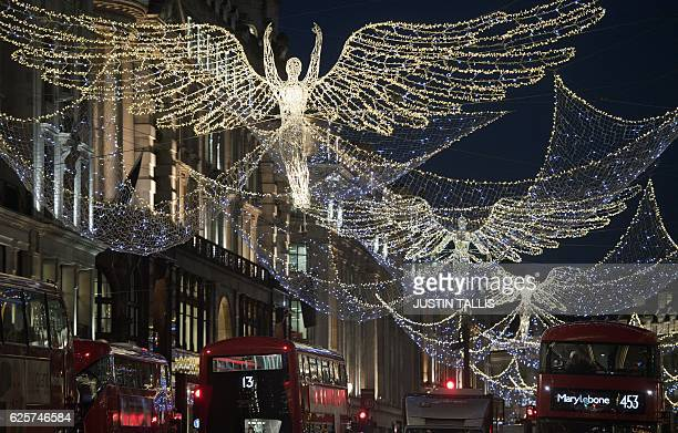 Red London busses pass beneath the Christmas festive lights on Regent Street in London on November 25 one month before Christmas Day / AFP / Justin...