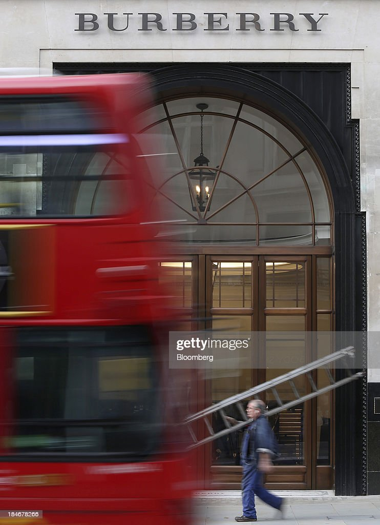 A red London double decker bus drives past the entrance to Burberry Group Plc's luxury clothing store on Regent Street in London, U.K., on Tuesday, Oct. 15, 2013. Burberry named Christopher Bailey as chief executive officer to succeed Angela Ahrendts who will leave in 2014 to work as a senior vice president at Apple Inc. Photographer: Chris Ratcliffe/Bloomberg via Getty Images