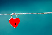 Tourism vacation and travel. Red love heart shaped lock padlock on bridge outdoor, blurred background
