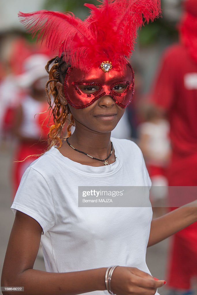 CONTENT] Red masked person during the Great Carnival Parade in the city of Cayenne