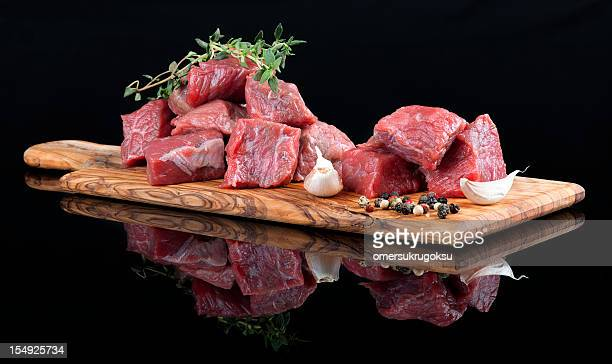 Red meat on wooden board, against black background