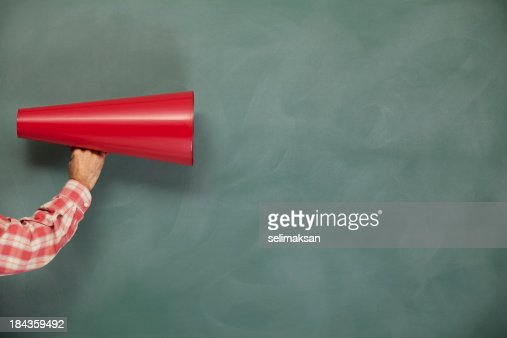 Red megaphone on green blank blackboard