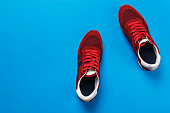 red men's sneakers on a blue background. casual shoes are out of fashion. place for text