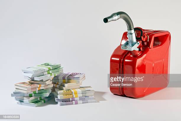 A red metal gas can next to stacks of large billed Euro banknotes