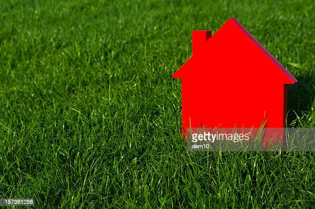 Red model house on green grass