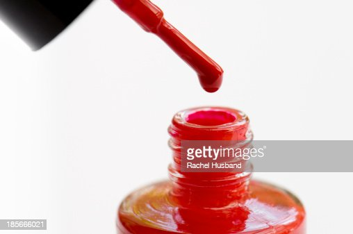 Red nail varnish dripping off brush into pot