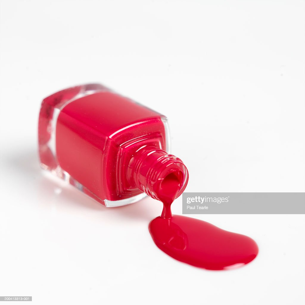 Red nail varnish spilling out of bottle, close up