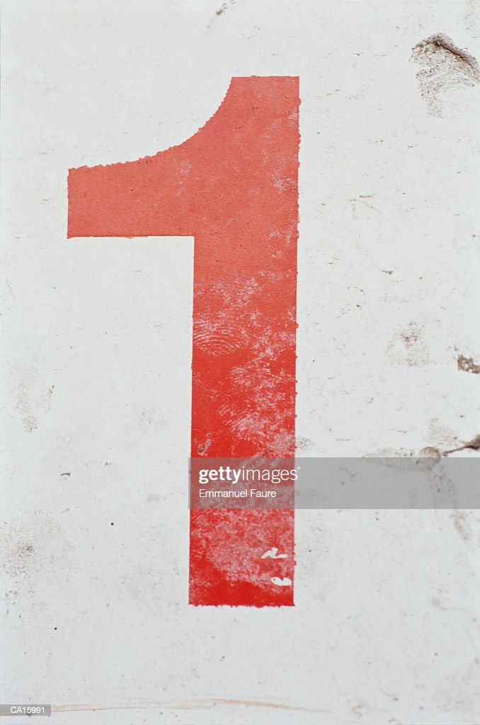 Red number '1' on white wall, close-up