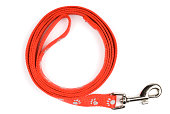 Red nylon dog lead or leash with paw print pattern on a white background. Soft shadow under lead.