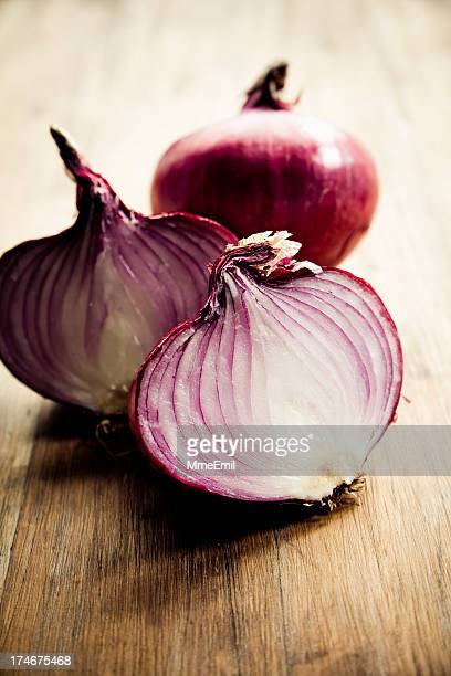 Red onion sliced into half on a wooden table
