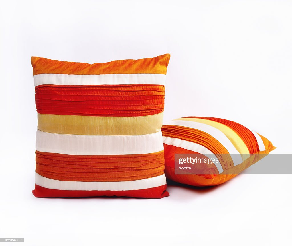 Red orange and white throw pillows on a white background
