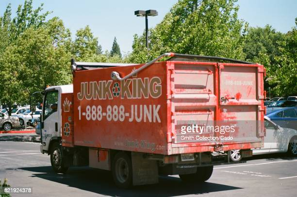 Red painted truck for the trash and junk removal company Junk King a regional franchised junk removal service driving through a parking lot in San...