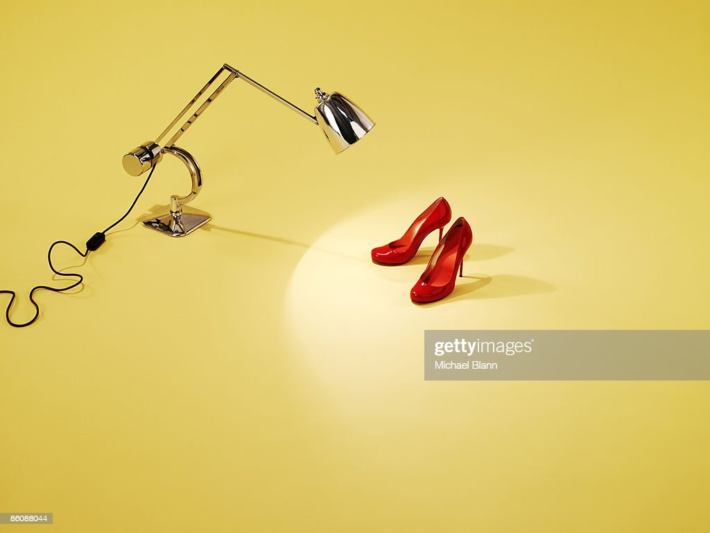 Red pair of shoes under anglepoise lamp : Stockfoto
