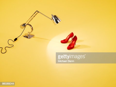 Red pair of shoes under anglepoise lamp : Photo