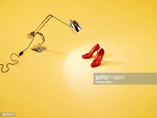 Red pair of shoes under anglepoise lamp