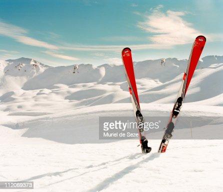 Red pair of ski in snow