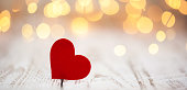 Valentine's day background. Red paper hearts on light bokeh background.