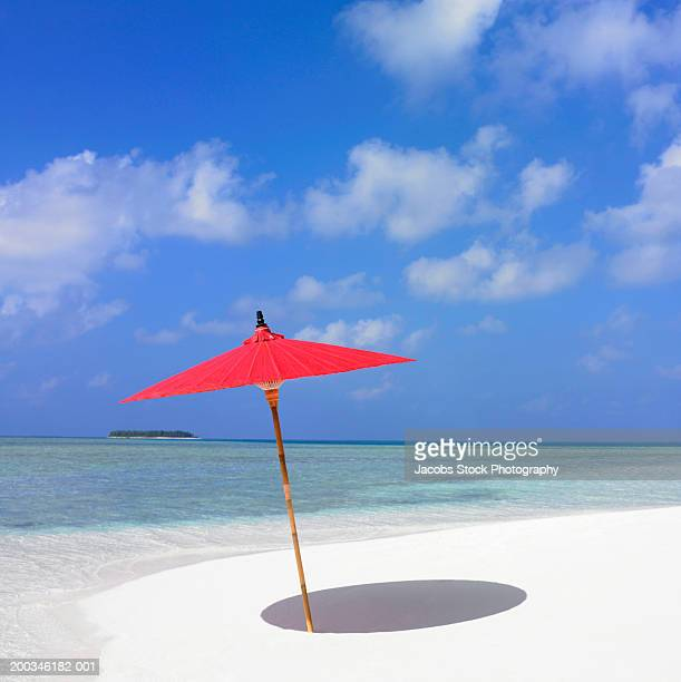 Red parasol in sand on beach