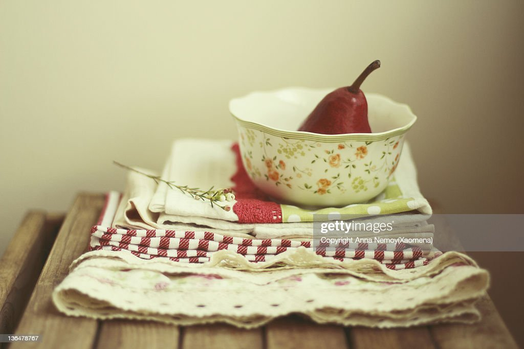Red pear in bowl and kitchen towels : Stock Photo