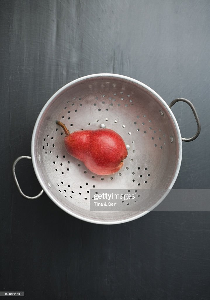 Red pear on a colander : Stock Photo