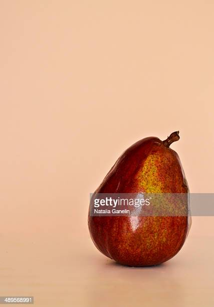 Red pear on tan/beige background