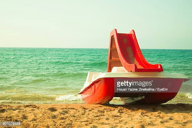 Red Pedal Boat At Shore Against Sky