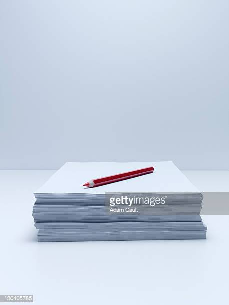 Red pencil on stack of paper