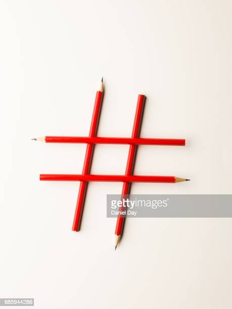 4 red pencils forming a hashtag