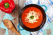 Red pepper soup topped with shredded cheese and green onions, overhead scene on rustic blue wood background