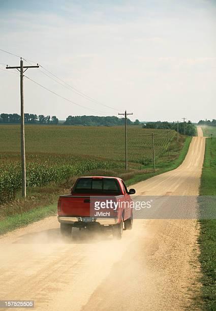 Red pickup truck on a dusty road in between fields