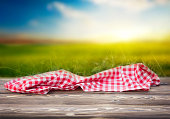 Red picnic table cloth on wooden table empty space nature sunset field background.Food advertisment template.