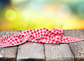 Red picnic table cloth napkin on wooden plank table blur nature background.Empty space table food design advertisement template.