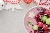 red pink and green smoothie bowl with cherry, melon, strawberry, raspberries and pomegranate , christmas fun food