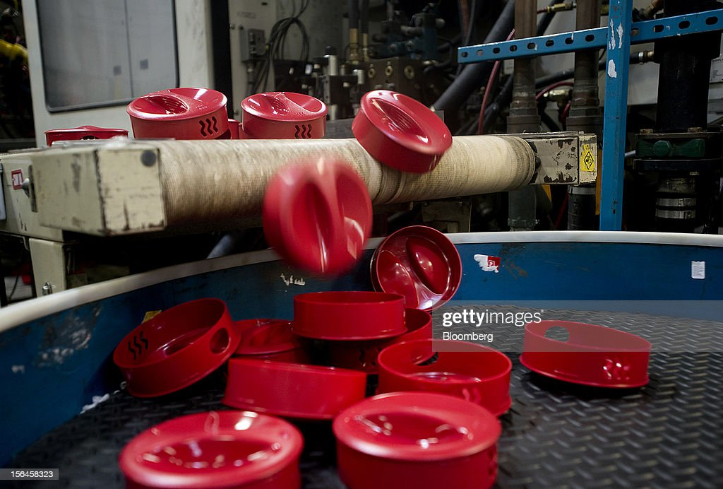 Red pitcher lids fall off a conveyor belt as they come out of the molding machine at the Newell Rubbermaid Inc. factory in Mogadore, Ohio, U.S., on Thursday, Nov. 15, 2012. The U.S. Federal Reserve is scheduled to release monthly industrial production data on Nov. 16. Photographer: Ty Wright/Bloomberg via Getty Images