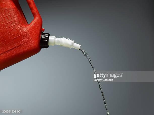 Red plastic can pouring petrol, close-up