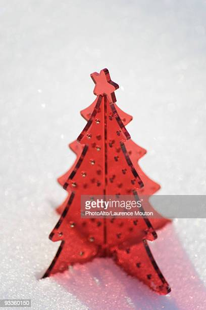 Red plastic Christmas tree decoration set in snow