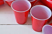 A close up image of empty red plastic drinking cups on a white picnic table.