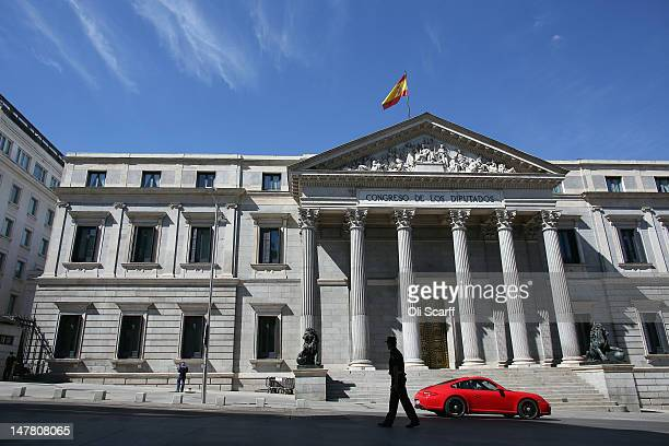 A red Porsche sports car drives past the Parliament building on July 2 2012 in Madrid Spain Despite having the fourth largest economy in the Eurozone...