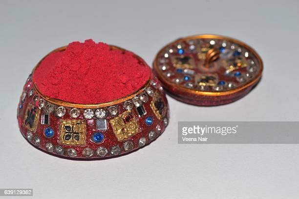 Red powder Kumkum/vermilion/sindoor in a decorated container