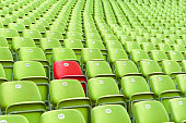 Empty Green Stadium Chairs, one of Private. Focus on Red Chair