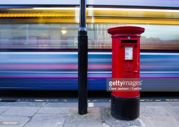 Red Public Mailbox Against Blurred Motion Of Bus