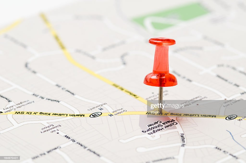A red push pin stuck in a street map