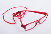 Red reading glasses with red neck strap attached to them, on a white surface.