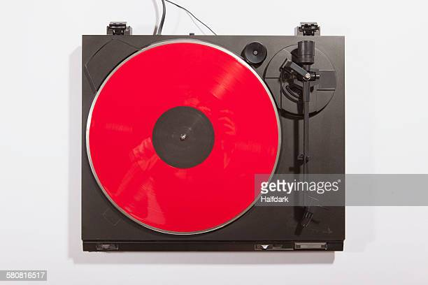 Red record playing on turntable on white background