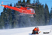 red rescue helicopter arriving after a ski accident in the Swiss Alps; Lech, Switzerland
