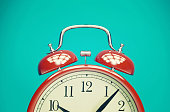 Red retro alarm clock on blue background with vintage filter