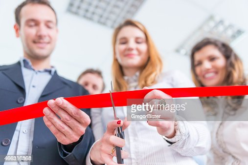 Red ribbon cutting ceremony from low angle