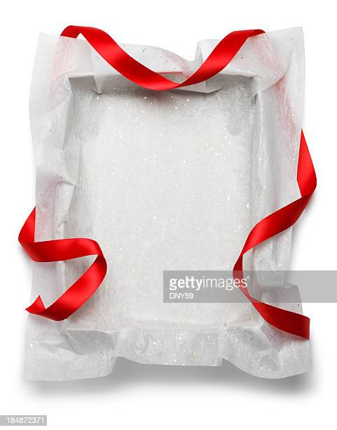 Red ribbon draped around empty gift box on white background