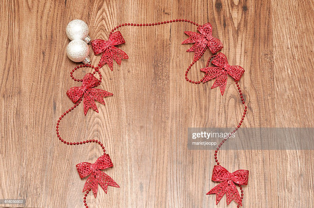 Red ribbon garland with two silver christmas tree baubles : Foto de stock